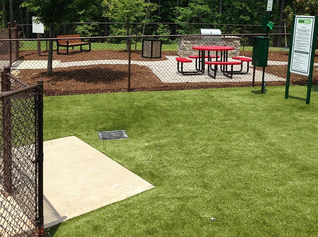 Picnic tables in the dog park at Brightleaf Apartments with K9Grass by ForeverLawn