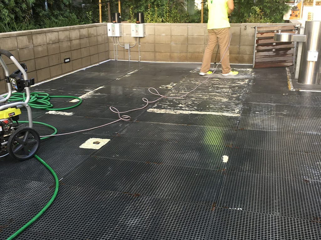ForeverLawn Pacific Coast team member spraying base of K9Grass installation
