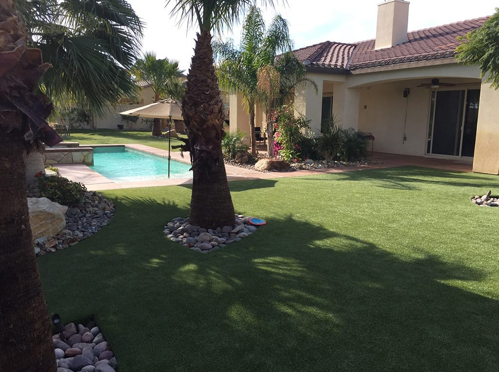 View of pool and house from backyard in Indio, CA with K9Grass installed by ForeverLawn Pacific Coast