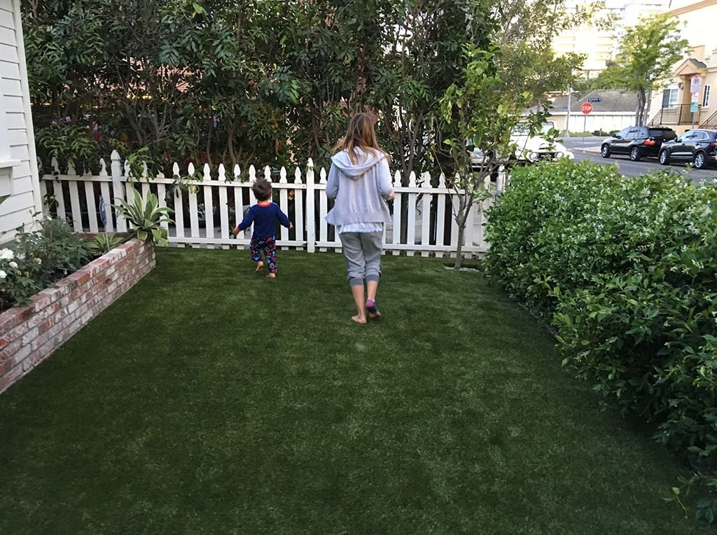 Mom and child running and playing on newly installed K9Grass in front yard