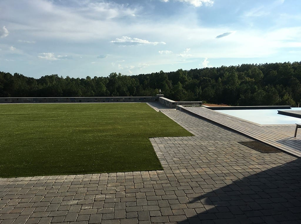View of backyard with K9Grass by ForeverLawn installed around infinity pool