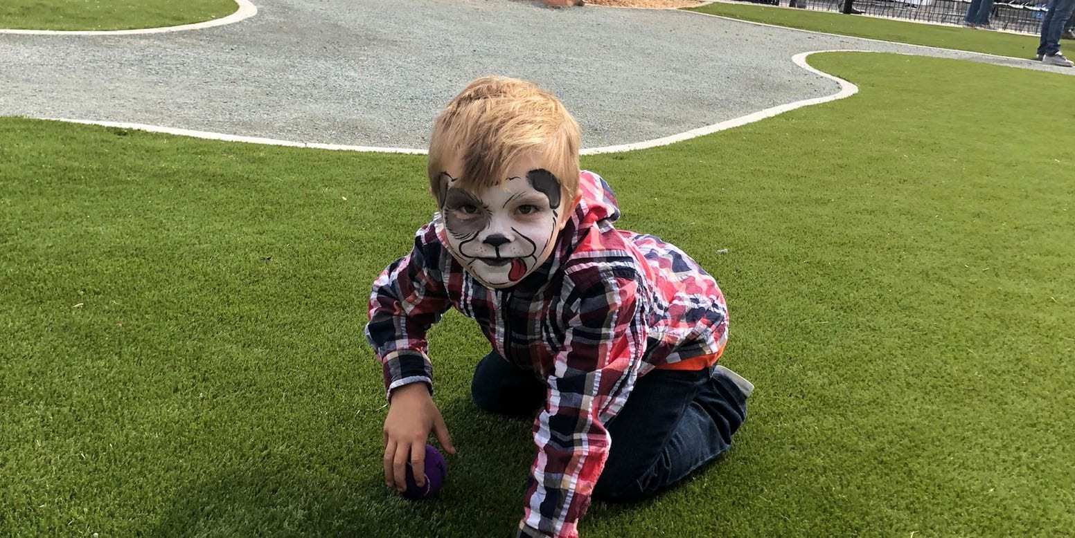 Child enjoying the K9Grass at Signal Hill Dog Park ribbon cutting ceremony in Long Beach, California